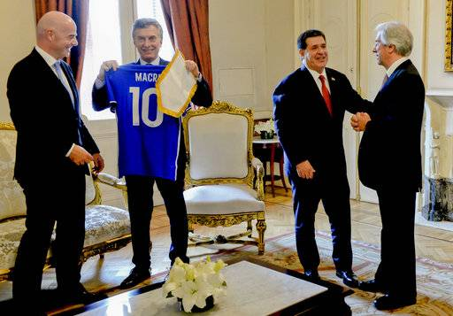 In this photo provided by the Argentine Presidency, Argentina's President Mauricio Macri, second left, looks at a soccer jersey with his name, next to FIFA President Gianni Infantino, left, as Paraguay's President Horacio Cartes, second right, talks to Uruguay's President Tavare Vazquez, right, at Casa Rosada in Buenos Aires, Argentina, Wednesday, Oct. 4, 2017. The three South American countries say they will chase a bid for the 2030 World Cup, which is expected to be competitive with China and Britain possibly in the mix. (Argentine Presidency via AP)