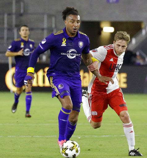 FILE - In this Sept. 27, 2017, file photo, Orlando City's Giles Barnes, front left, and New England Revolution's Scott Caldwell battle for possession of the ball during the first half of an MLS soccer match, in Orlando, Fla. Three Orlando City soccer players were kicked out of Disney World after officials say they became verbally aggressive with park security and other guests. An Orange County Sheriff's Office report says Orlando City Lions players Donald Toia and Giles Barnes, along with U.S. women's national team standout and Orlando City Pride star Alex Morgan, were all escorted out of Disney World's Epcot park on Sunday, Oct. 1, 2017. Toia's wife was also ejected. The report says the group began arguing with other guests and workers after Barnes cut in line at the United Kingdom pavilion's pub.