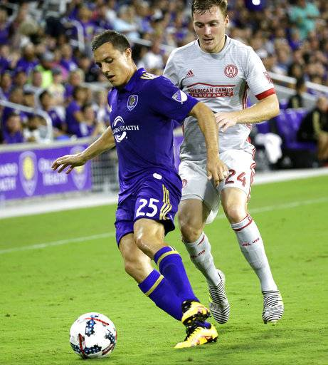 FILE - In this July 21, 2017, file photo, Orlando City's Donald Toia (25) gets position in front of Atlanta United's Julian Gressel (24) during the second half of an MLS soccer match, in Orlando, Fla. Three Orlando City soccer players were kicked out of Disney World after officials say they became verbally aggressive with park security and other guests. An Orange County Sheriff's Office report says Orlando City Lions players Donald Toia and Giles Barnes, along with U.S. women's national team standout and Orlando City Pride star Alex Morgan, were all escorted out of Disney World's Epcot park on Sunday, Oct. 1, 2017. Toia's wife was also ejected. The report says the group began arguing with other guests and workers after Barnes cut in line at the United Kingdom pavilion's pub.
