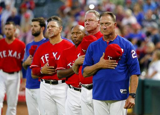 FILE- In this Thursday, Sept. 28, 2017, file photo, Texas Rangers manager Jeff Banister, right, staff and players stand during the playing of the national anthem before a baseball game against the Oakland Athletics in Arlington, Texas.