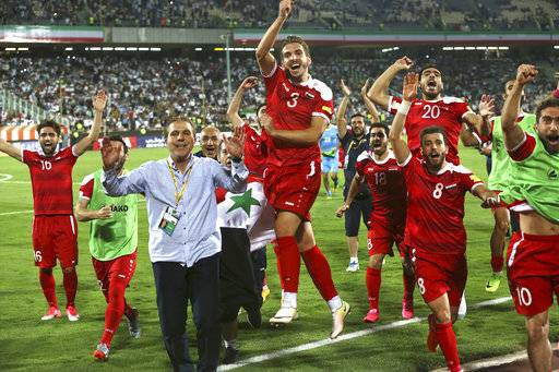 FILE - In this Sept. 5, 2017 file photo, Syria's national soccer team celebrates at the conclusion of their match with Iran which drew 2-2 during their Round 3 - Group A World Cup qualifier at the Azadi Stadium in Tehran, Iran.  Regardless of how Syria does in its World Cup playoff against Australia, the team has helped football knock fighting out the headlines for a while in their war-torn country. The Syrians are still in contention to qualify for the World Cup for the first time, and the journey to their biggest match so far has captured domestic and international attention.