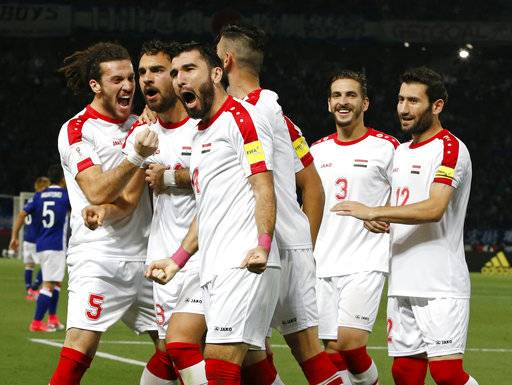 FILE - In this June 7, 2017 file photo, Syria's Mardek Mardkian, second from left, celebrates a goal with teammates during their international friendly soccer match against Japan in Tokyo. Regardless of how Syria does in its World Cup playoff against Australia, the team has helped football knock fighting out the headlines for a while in their war-torn country. The Syrians are still in contention to qualify for the World Cup for the first time, and the journey to their biggest match so far has captured domestic and international attention.