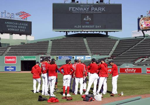 Boston Red Sox pitchers gather for a meeting in the outfield during a workout at Fenway Park in Boston, Tuesday, Oct. 3, 2017. The Red Sox face the Houston Astros in the American League Division playoff series.