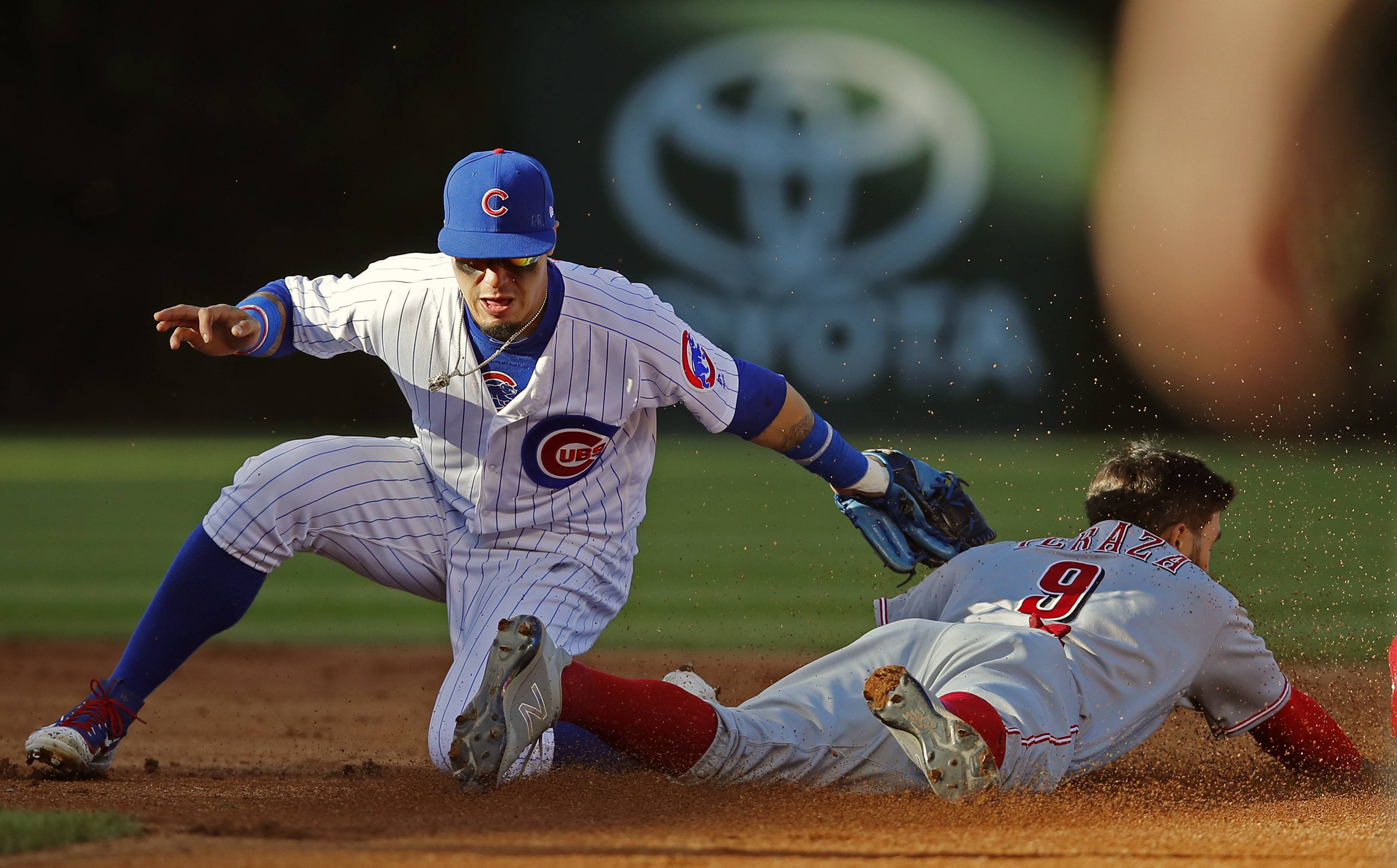 Chicago Cubs' Javier Baez, left, tags out Cincinnati Reds' Jose Peraza attempting to steal second base during the fifth inning of a baseball game Saturday, Sept. 30, 2017, in Chicago.