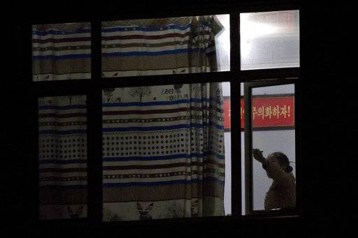 "In this Sept. 4, 2017, photo, a woman closes the window to a room where the slogan ""Let's Follow the Ideas!"" hangs on the wall in a dormitory for workers with the seafood processing factory Hunchun Pagoda, in the city of Hunchun in northeastern China's Jilin province. North Korean workers, outsourced by their government to process seafood at the plant that ends up in American stores and homes, are paid a fraction of their salaries. The rest, as much as 70 percent, is taken by North Korea's government."