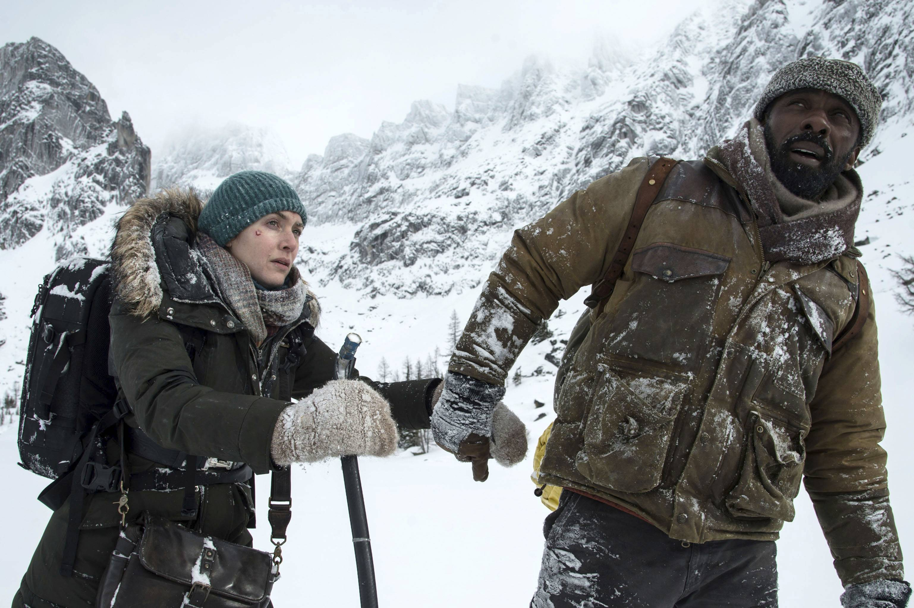 "A photojournalist (Kate Winslet), left, and a neurosurgeon (Idris Elba) fight to survive when their plane crashes in ""The Mountain Between Us."""