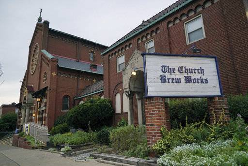 In this Aug. 7, 2017 photo, the Church Brew Works, a brewery operating in a renovated church, stands in Pittsburgh. At the Church Brew Works, an early church-turned-brewery that opened in 1996, patrons slide into booths crafted from pews. Breweries opening in renovated churches are winning fans but earning disapproval from clergy and worshippers across the U.S.