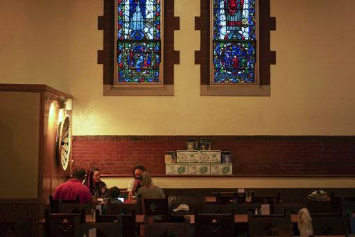 In this Aug. 7, 2017 photo, patrons sit beneath stained glass windows at the Church Brew Works, a former church renovated into a brewery, in Pittsburgh. Breweries opening in renovated churches are winning fans but earning disapproval from clergy and worshippers across the U.S.