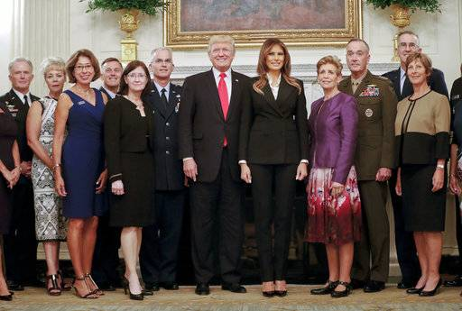 President Donald Trump and first lady Melania Trump, center, poses for a group photo with senior military leaders and spouses in the State Dining Room of the White House in Washington, Thursday, Oct. 5, 2017. Trump was hosting the dinner for the group.