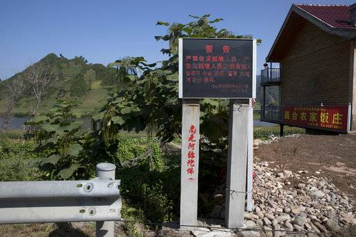 In this Aug. 30, 2017 photo, a board warns against harboring people who cross the border is displayed near Lingjiang on the border with North Korea in northeastern China's Jilin province. Securing North Korea's missile launchers and nuclear, chemical and biological weapons sites would likely be a chief priority for China in the event of a major crisis involving its communist neighbor, analysts say, although Beijing so far is keeping mum on any plans.