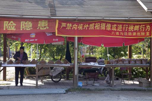 "In this Aug. 30, 2017 photo, a tobacco vendor waits for customers near banners which read ""Strictly prohibited from taking photos across the border or making provocative actions"" near Lingjiang on the border with North Korea in northeastern China's Jilin province. Securing North Korea's missile launchers and nuclear, chemical and biological weapons sites would likely be a chief priority for China in the event of a major crisis involving its communist neighbor, analysts say, although Beijing so far is keeping mum on any plans."