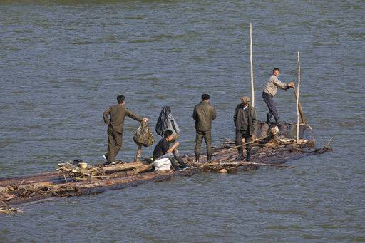 In this Aug. 30, 2017 photo, North Korean men ride on a make shift raft to transport logs down the river that divides North Korea from China near the Chinese city of Lingjiang in northeastern China's Jilin province. Securing North Korea's missile launchers and nuclear, chemical and biological weapons sites would likely be a chief priority for China in the event of a major crisis involving its communist neighbor, analysts say, although Beijing so far is keeping mum on any plans.