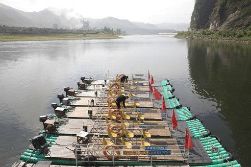 In this Aug. 29, 2017 photo, Chinese men prepare rafts for tourists visiting the river that divides China from North Korea on the left near the Chinese city of Jian in northeastern China's Jilin province. Securing North Korea's missile launchers and nuclear, chemical and biological weapons sites would likely be a chief priority for China in the event of a major crisis involving its communist neighbor, analysts say, although Beijing so far is keeping mum on any plans.