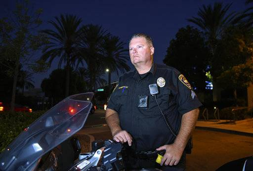 Chula Vista police officer Fred Rowbotham stands next to his motorcycle Thursday, Oct. 5, 2017, in Chula Vista, Calif. Rowbotham was injured at the Las Vegas shooting while attending the concert with his wife and friends. The Sunday night crowd of about 20,000 country music fans happened to include many off-duty police and firefighters like Rowbotham, who sprang into the role of first responders when tragedy struck and played an important role in saving lives.
