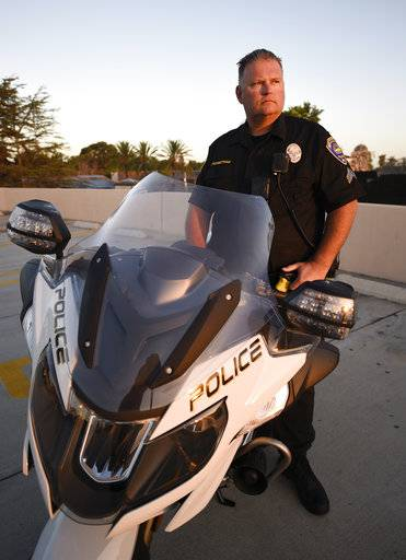 Chula Vista police officer Fred Rowbotham stands next to his motorcycle Thursday, Oct. 5, 2017 in Chula Vista, Calif. Rowbotham was injured at the Las Vegas shooting while attending the concert with his wife and friends. The Sunday night crowd of about 20,000 country music fans happened to include many off-duty police and firefighters, who sprang into the role of first responders when tragedy struck and played an important role in saving lives.