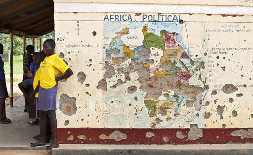 FILE - In this Nov. 15, 2016 file photo, students line up outside a classroom with a map of Africa on its wall, in Yei, in southern South Sudan. The United States is poised to permanently lift sanctions on Sudan, U.S. officials said Oct. 5, 2017, recognizing the long-estranged country's progress on human rights and counterterrorism after decades of war and abuses. The Trump administration will complete a process that former President Barack Obama started in January, when he temporarily lifted the penalties.
