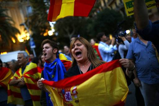 Anti-independence demonstrators waving Spanish flags shout slogans during a protest in Barcelona, Wednesday, Oct. 4, 2017. Catalonia's regional government is mulling when to declare the region's independence from Spain in the wake of a disputed referendum that has triggered Spain's most serious national crisis in decades.