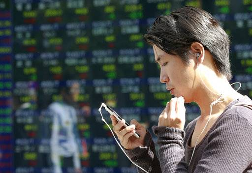 A man uses a smartphone in front of an electronic stock indicator of a securities firm in Tokyo, Thursday, Oct. 5, 2017. Share prices mostly rose in Asia on Thursday following a day of meager gains on Wall Street. Investors are awaiting a U.S. government jobs data following a report by payroll processor ADP showing that hiring by private employers weakened sharply last month, partly because of the damage done by hurricanes Harvey and Irma.