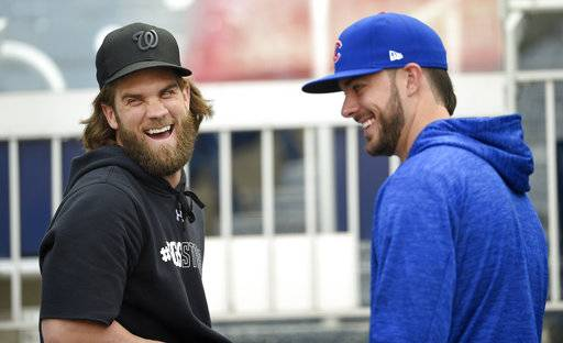 Washington Nationals' Bryce Harper, left, laughs with Chicago Cubs' Kris Bryant, right, at Nationals Park, Thursday, Oct. 5, 2017, in Washington. Game 1 of the National League Division Series is on Friday.