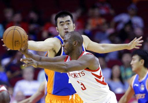 Shanghai Sharks center Zhang Zhaoxu (23) tries to defend against the pass by Houston Rockets guard Chris Paul (3) in the first half of an NBA exhibition basketball game Thursday, Oct. 5, 2017, in Houston.