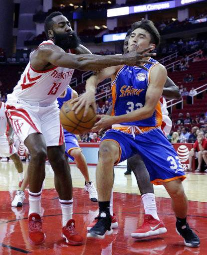 Houston Rockets guard James Harden (13) defends the low pass from Shanghai Sharks guard Jimmer Fredette (32) in the first half of an NBA exhibition basketball game Thursday, Oct. 5, 2017, in Houston.