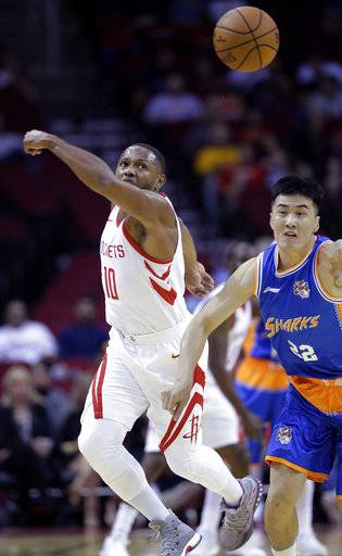 Houston Rockets guard Eric Gordon (10) and Shanghai Sharks forward Zhai Yi (22) chase a loose ball in the first half of an NBA exhibition basketball game Thursday, Oct. 5, 2017, in Houston.