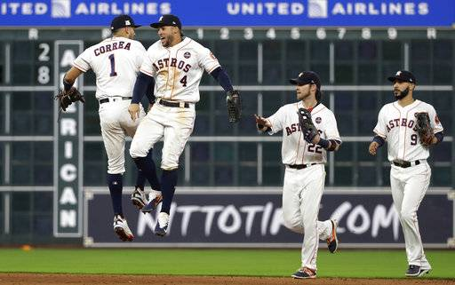 Houston Astros' Carlos Correa (1), George Springer (4), Josh Reddick (22) and Marwin Gonzalez (9) celebrate their win over the Boston Red Sox in Game 1 of baseball's American League Division Series, Thursday, Oct. 5, 2017, in Houston. Houston won 8-2.
