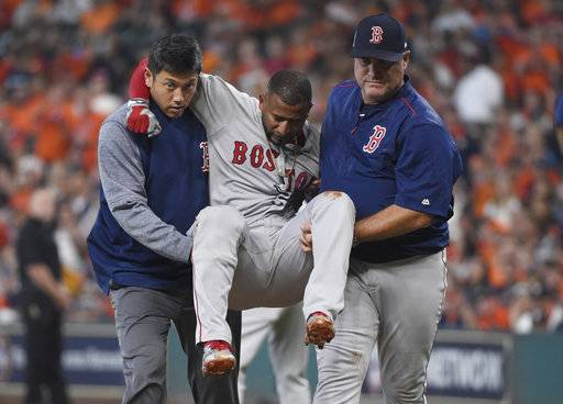 Boston Red Sox designated hitter Eduardo Nunez, center, is carried off the field after he was injured running to first base during the first inning in Game 1 of baseball's American League Division Series against the Houston Astros, Thursday, Oct. 5, 2017, in Houston.