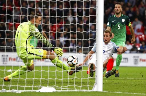 England's Harry Kane, center, scores the opening goal during the World Cup Group F qualifying soccer match between England and Slovenia at Wembley stadium in London, Thursday, Oct. 5, 2017.