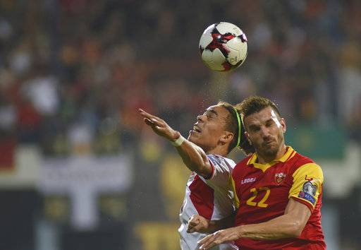 Denmark's Yussuf Poulsen, left, challenges Montenegro's Marko Simic, during their World Cup Group E qualifying soccer match at the City Stadium in Podorica, Montenegro, Thursday, Oct. 5, 2017.
