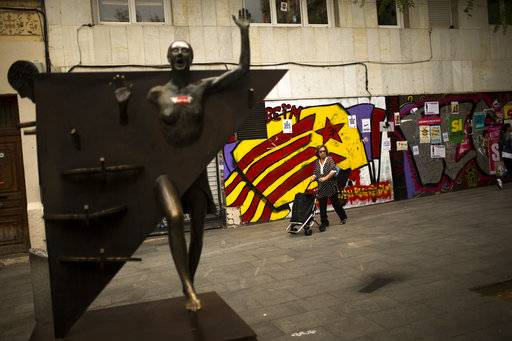 "A woman pushes a trolley past a graffiti of an ""estelada"", or Catalonia independence flag, at the Gracia neighborhood in Barcelona, Wednesday, Oct. 4, 2017. Catalonia's regional government is mulling when to declare the region's independence from Spain in the wake of a disputed referendum that has triggered Spain's most serious national crisis in decades."