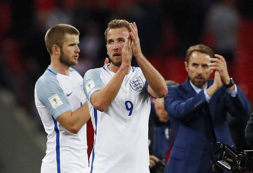 England's Harry Kane, center, and England manager Gareth Southgate, right, applaud the supporters at the end of the World Cup Group F qualifying soccer match between England and Slovenia at Wembley stadium in London, Thursday, Oct. 5, 2017. Kane scored the goal in England's 1-0 win that qualifies the team for the tournament finals.