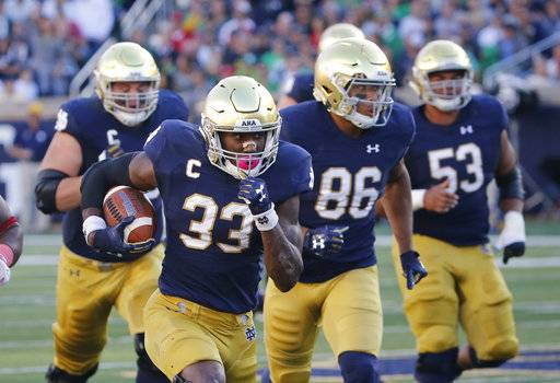 FILE - In this Sept. 30, 2017, file photo, Notre Dame running back Josh Adams heads for the end zone on a touchdown run during the first half of an NCAA college football game against Miami (Ohio) in South Bend, Ind. Adams is averaging 131.6 yards through five games to go with four touchdowns. The 6-2, 225-pound junior is determined to finish every run and get in the end zone, where the Irish are a perfect 22 for 22 in the red zone, one of 12 FBS teams to remain unblemished in that category.