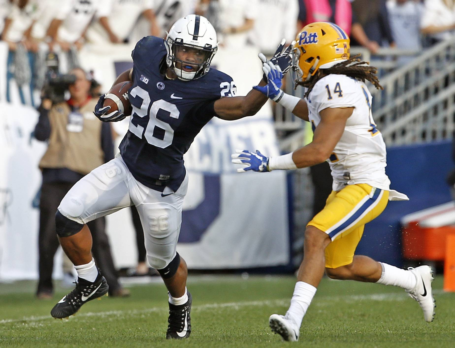 FILE - In this Saturday, Sept. 9, 2017 file photo, Penn State's Saquon Barkley (26) looks to stiff arm Pittsburgh's Avonte Maddox (14) during the second half of an NCAA college football game in State College, Pa. Penn State coach James Franklin sees the talent Northwestern has and the success the Wildcats have experienced under Pat Fitzgerald. Running back Saquon Barkley keeps padding his Heisman Trophy resume.