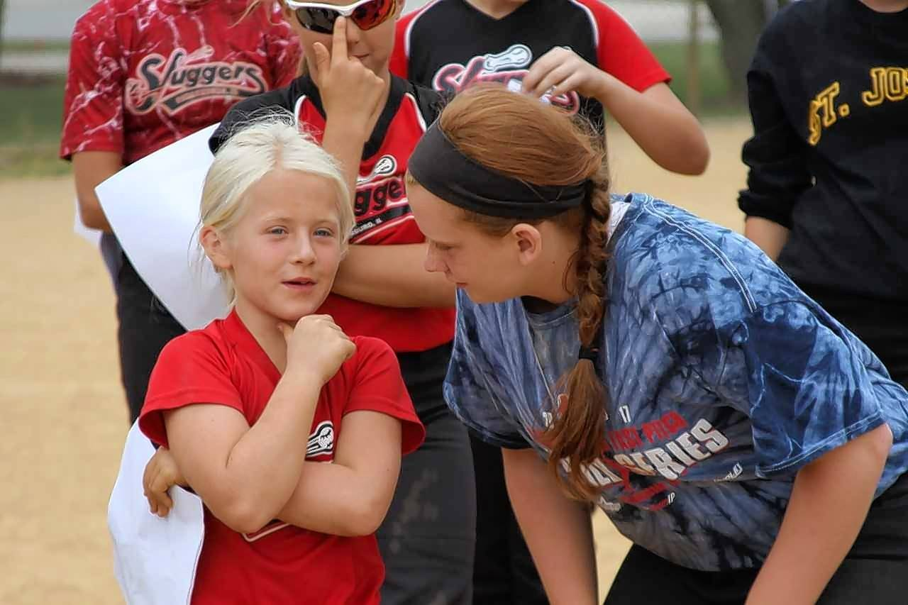 Cassie M. encourages a younger Slugger to tell the team how to sprint to a ground ball.