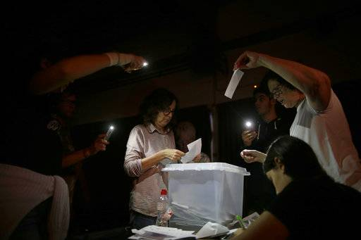 FILE, In this Sunday, Oct. 1, 2017 file photo, volunteers, acting as polling station officials, start to count ballots during a blackout after the polling station closed at the La Llacuna school in the Poble Nou neighborhood in Barcelona, Spain. The ballot boxes arrived from France in the dead of night, were stored in homes and improvised hidey-holes, and then secretly shuttled to polling stations across Catalonia right under the nose of police.