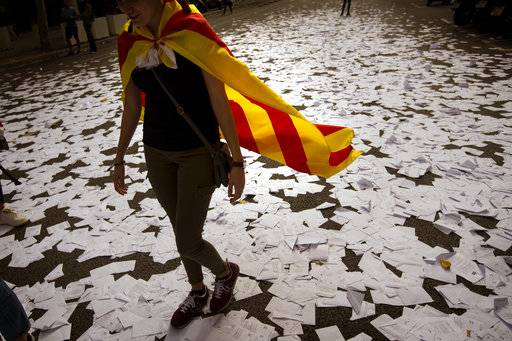 FILE, In this Sunday, Oct. 1, 2017 file photo, a woman wearing an estelada or independence flag walks a long a street covered with referendum ballots thrown by pro-independence demonstrators, during a rally in front of the Spanish Partido Popular ruling party headquarters in Barcelona, Spain. The ballot boxes arrived from France in the dead of night, were stored in homes and improvised hidey-holes, and then secretly shuttled to polling stations across Catalonia right under the nose of police.