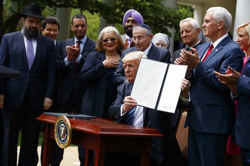 FILE - In this May 4, 2017 file photo, President Donald Trump holds up a signed executive order aimed at easing an IRS rule limiting political activity for churches in the Rose Garden of the White House in Washington.  In an order that undercuts federal protections for LGBT people, Attorney General Jeff Sessions issued a sweeping directive to agencies Friday to do as much as possible to accommodate those who claim their religious freedoms are being violated.  Trump announced plans for the directive last May in a Rose Garden ceremony where he was surrounded by religious leaders. Since then, religious conservatives have anxiously awaited the Justice Department guidance.
