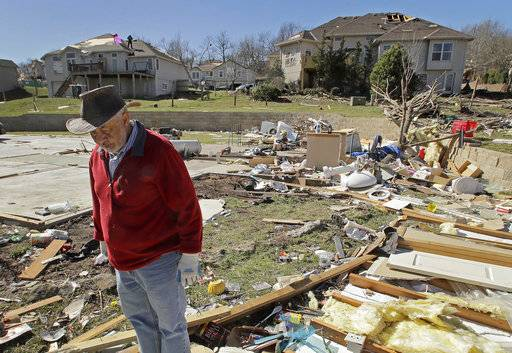 FILE - In this March 7, 2017, file photo, Mark Swartz salvage items from his son's home that was destroyed by a tornado after a severe storm passed through Oak Grove, Mo. If you think this has been a wild and costly year for weather disasters, federal meteorologists say you are right, it's been record setting. So far this year the United States has had 15 weather disasters that caused at least $1 billion in damages.