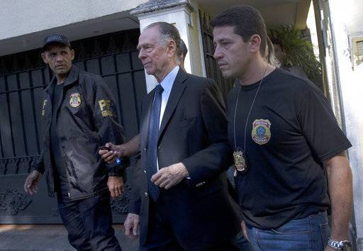 Carlos Nuzman, President of the Brazilian Olympic Committee, center, is escorted by federal police officers after being taken into custody at his home, in Rio de Janeiro, Brazil, Thursday, Oct. 5, 2017. The president of the Brazilian Olympic Committee was arrested amid an investigation into a vote-buying scheme to bring the Olympics to Rio de Janeiro last year.