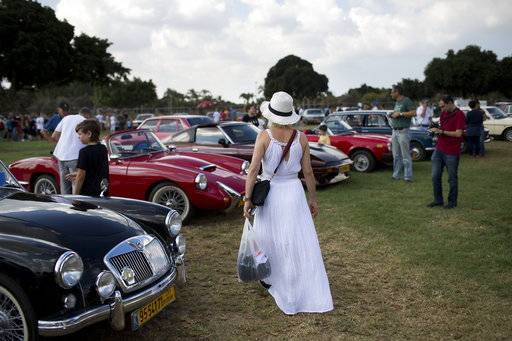 "People look at antique cars during the 31st annual ""Five Club"" car collectors' meeting in Ramat Gan, Israel, Friday, Oct. 6, 2017. Each weekend, at Israeli gas stations and parking lots and parks, car collectors gather with their beauties _ and take a step back in time."