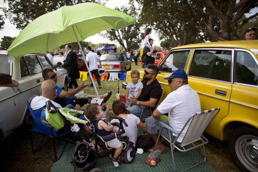 "People sits next to their antique cars during the 31st annual ""Five Club"" collectors car meeting in Ramat Gan, Israel, Friday, Oct. 6, 2017."