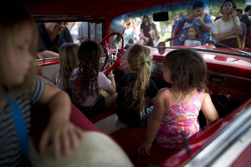"Children sit in their grandfather's antique car during the 31st annual ""Five Club"" collectors car meeting in Ramat Gan, Israel, Friday, Oct. 6, 2017."