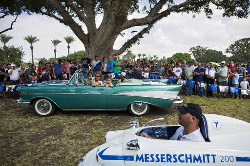 "Spectators looks at 1957 Chevy Bel Air and 1957 Messerschmitt during the 31st annual ""Five Club"" car collectors' meeting in Ramat Gan, Israel, Friday, Oct. 6, 2017. Each weekend, at Israeli gas stations and parking lots and parks, car collectors gather with their beauties _ and take a step back in time."