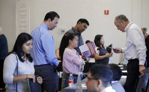 In this Thursday, Aug. 24, 2017, photo, Phil Wiggett, right, a recruiter with the Silicon Valley Community Foundation, looks at a resume during a job fair in San Jose, Calif. On Friday, Oct. 6, 2017, the U.S. government issues the September jobs report.