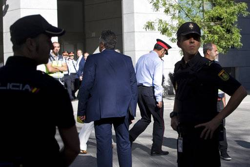 Catalan regional police chief Josep Luis Trapero walks past national police officers as he leaves the national court in Madrid, Spain, Friday, Oct. 6, 2017. Spain's National Court is questioning two senior officers of Catalonia's regional police force and the leaders of two pro-independence civic groups who have been placed under investigation for sedition, a case over preparations for an Oct. 1 referendum on independence.