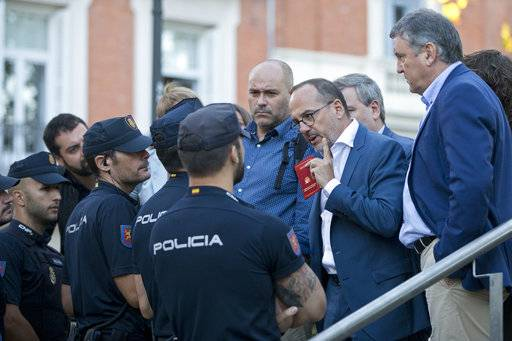 Parliamentary deputies argue with police who wouldn't let them get close when Catalan regional police chief Josep Luis Trapero arrived at the national court in Madrid, Spain, Friday, Oct. 6, 2017. A Spanish judge is due to question Mossos d'Esquadra chief Trapero and two pro-independence campaigners about their role in an Oct. 1 referendum that the Spanish government declared as illegal.