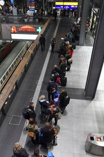 Passengers queue in the main train station in Berlin, Friday, Oct. 6, 2017. Seven people died Thursday as high winds knocked over trees and caused widespread travel chaos in northern Germany. Train connections in several northern states were shut down, including links to and from Berlin, because of the danger from branches over the tracks. Germany rail company Deutsche Bahn opened stationary trains to travelers left stranded by cancellations. (Maurizio Gambarini/dpa via AP)