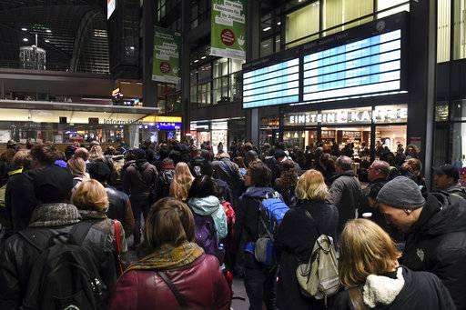 Passengers crowd in the main train station in Berlin, Friday, Oct. 6, 2017. Seven people died Thursday as high winds knocked over trees and caused widespread travel chaos in northern Germany. Train connections in several northern states were shut down, including links to and from Berlin, because of the danger from branches over the tracks. Germany rail company Deutsche Bahn opened stationary trains to travelers left stranded by cancellations. (Maurizio Gambarini/dpa via AP)