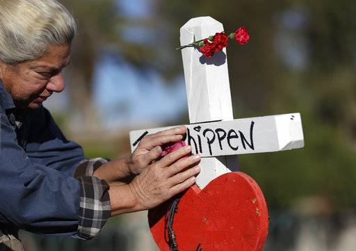 Nancy Hardy, of Las Vegas, touches a flower on a cross placed in honor of mass shooting victim John Phippen, of Santa Clarita, Calif., Friday, Oct. 6, 2017, in Las Vegas. A gunman opened fire on an outdoor music concert on Sunday killing dozens and injuring hundreds.